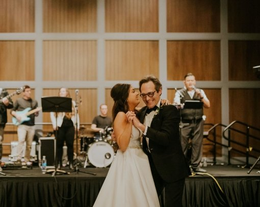 Bride dancing with her father in front of a live band